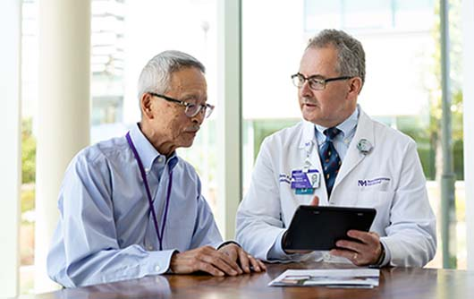 A male physician discussing a scan on an iPad with an elderly male patient.