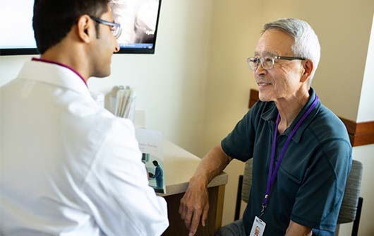 A male physician meeting with an elderly male patient.