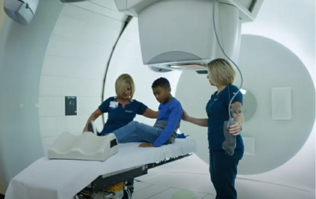 A pediatric proton therapy patient is helped onto the scan bed by two nurses.